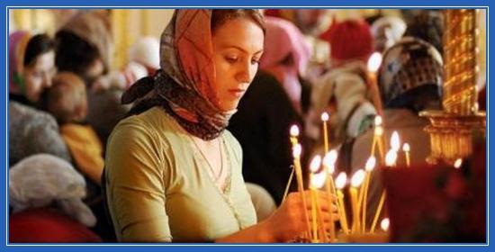 Молитва в храме. Девушка ставит свечи
