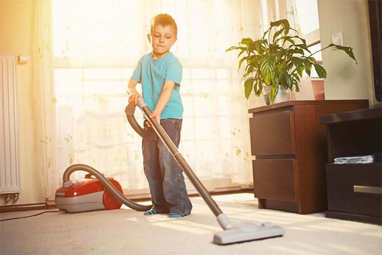 Мальчик пылесосит. Уборка квартиры