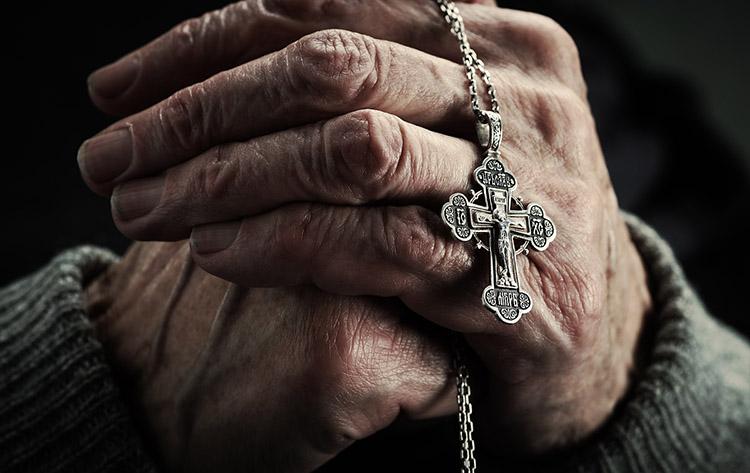 Нательный крест в руках