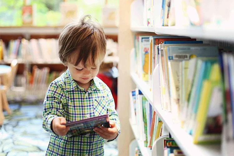 Ребенок берет книгу с полки