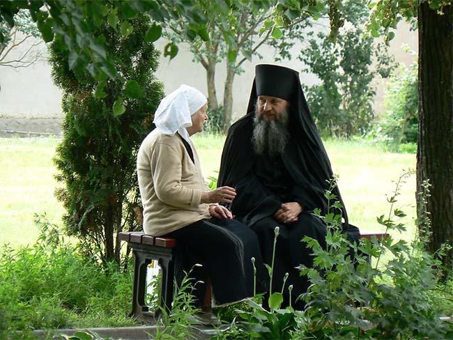 Женщина беседует с батюшкой
