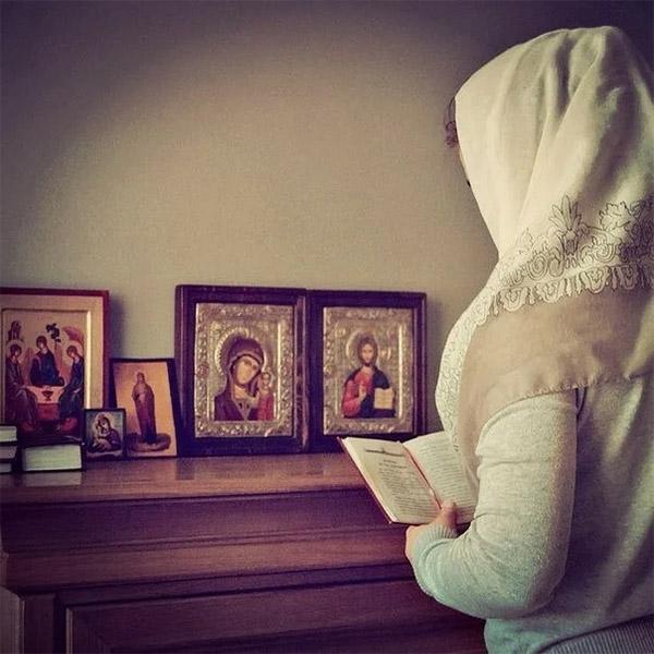 Молится дома перед иконами