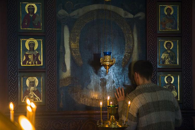 Мужчина в храме у иконы