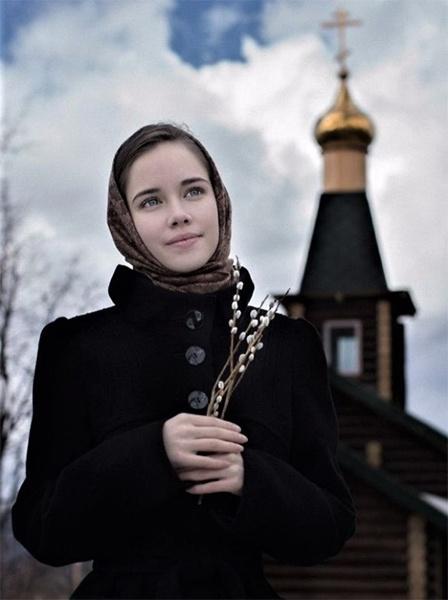 Женщина с вербой на фоне храма