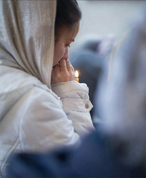 Женщина со свечой в храме
