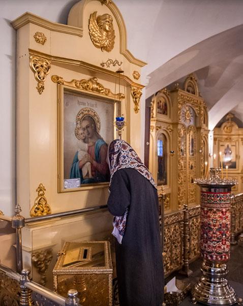 Женщина у иконы в храме