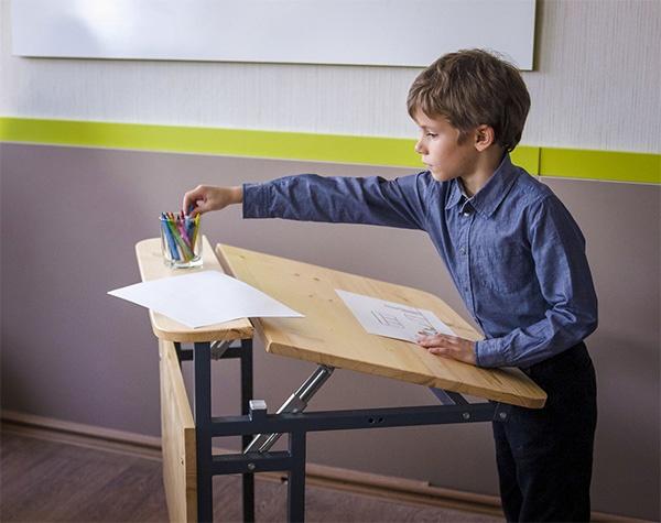 Мальчик рисует за конторкой