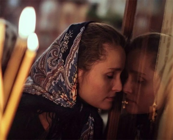 Женщина в храме прикладывается к иконе