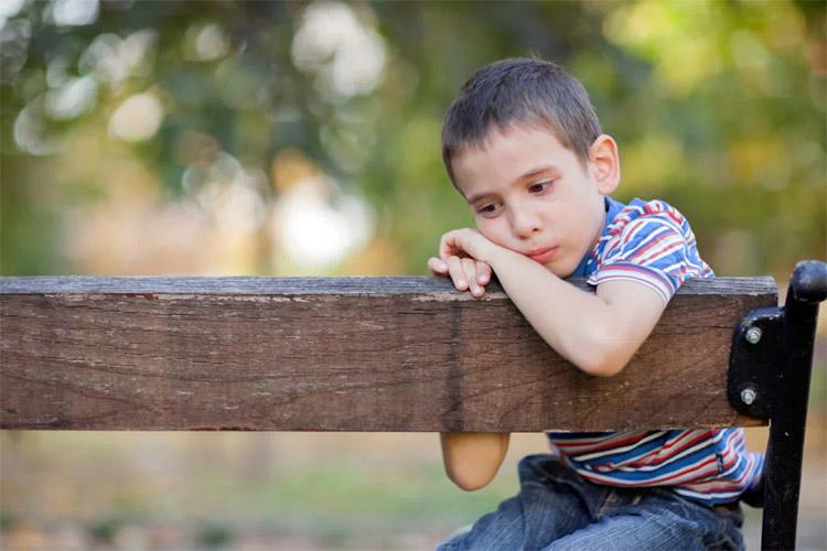 Грустный мальчик на скамейке