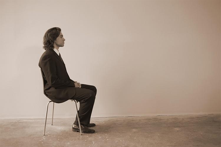 Мужчна в пустой комнате на стуле