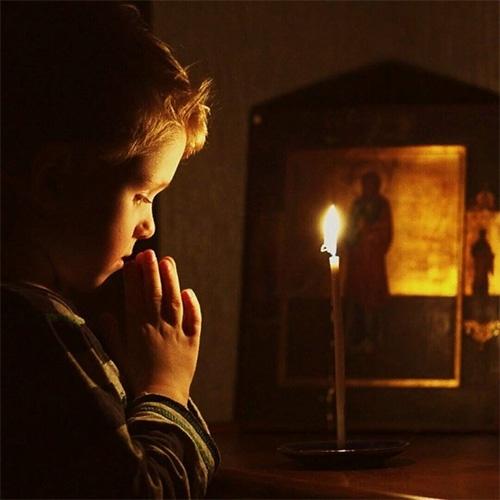 Ребенок молится перед иконой