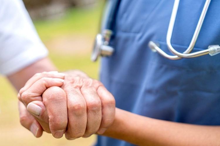 Врач держит за руку пациента