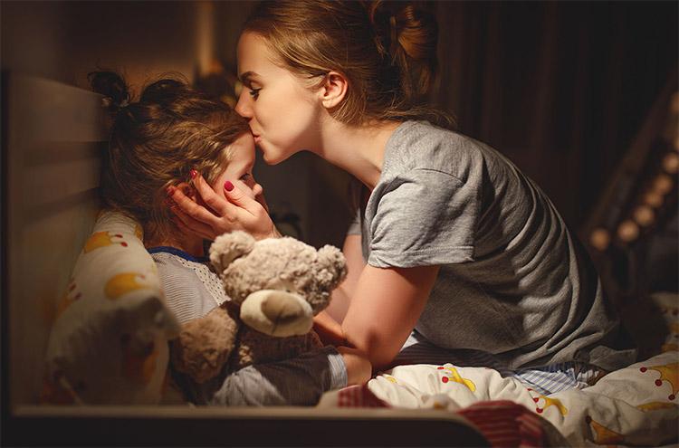 Мама обнимает дочку перед сном