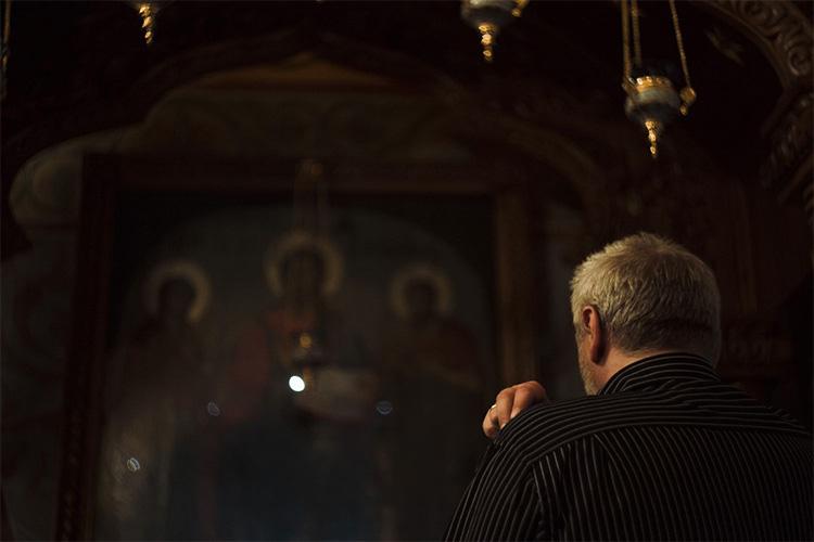 Мужчина перед иконой в храме