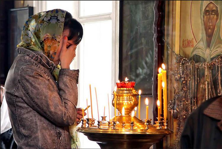 Женщина перед иконой Матроны Московской в храме