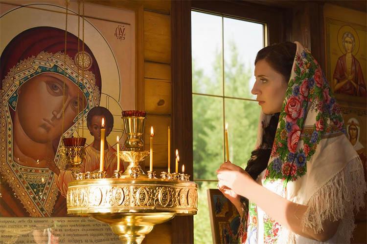Женщина со свечкой перед образом Пресвятой Богородицы