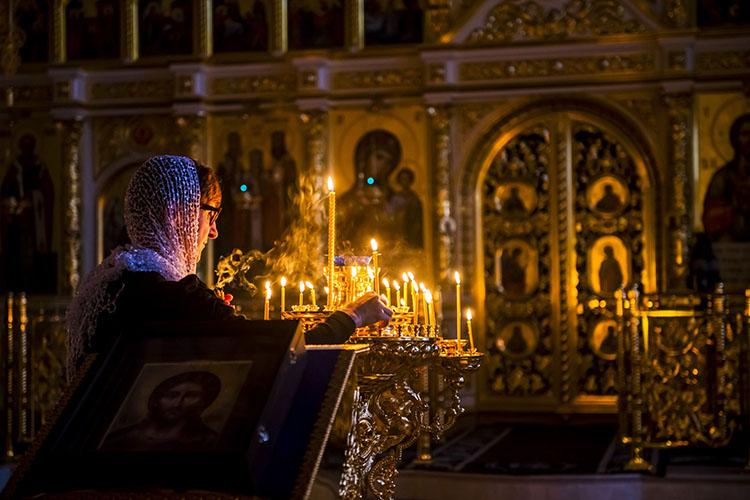 Женщина ставит свечку в храме