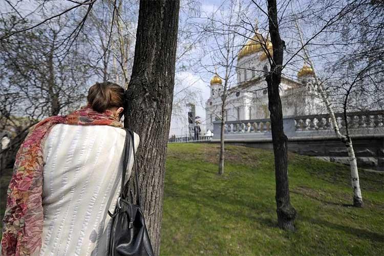 Женщина у дерева напротив храма