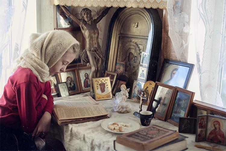 Девочка читает перед иконами