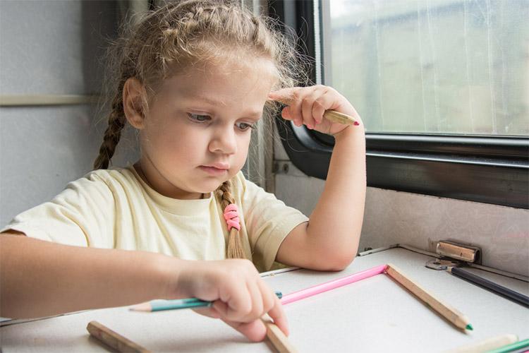 Девочка рисует в поезде
