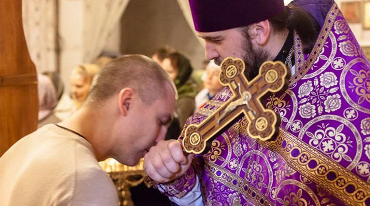 Мужчина целует руку священника
