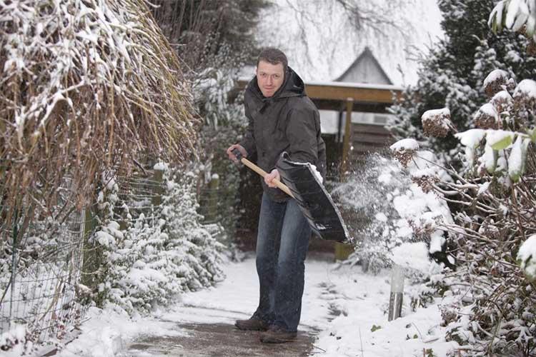 Мужчина убирает снег