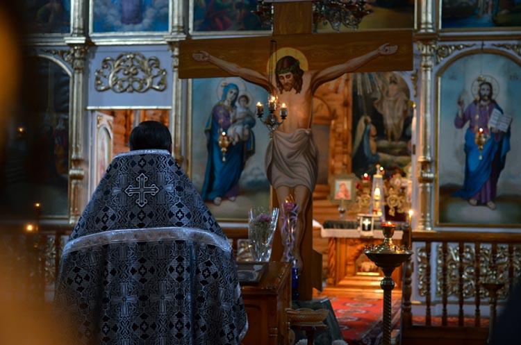 Священник в храме перед Распятием Христа