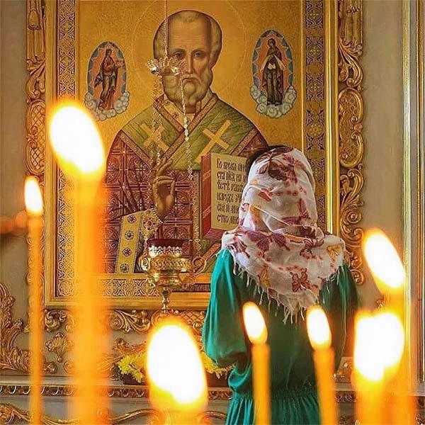 Женщина перед иконой святителя Николая
