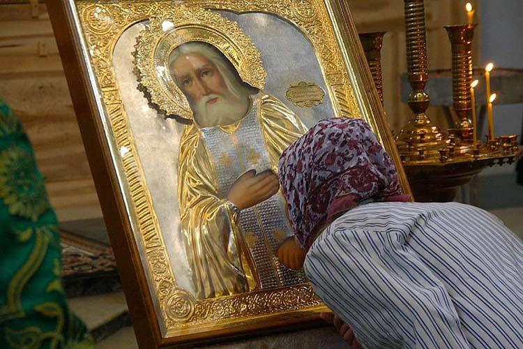 Женщина у иконы батюшки Серафима