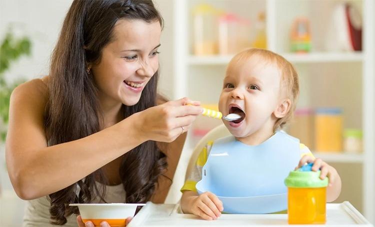 Мама кормит ребенка кашей