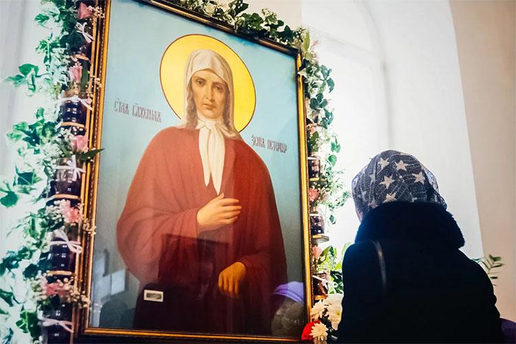Женщина перед иконой блаженной Ксении петербургской