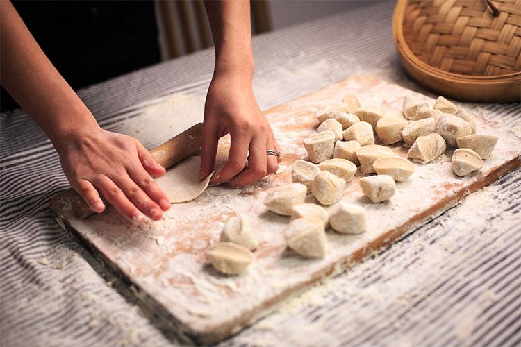 Женщина раскатывает тесто
