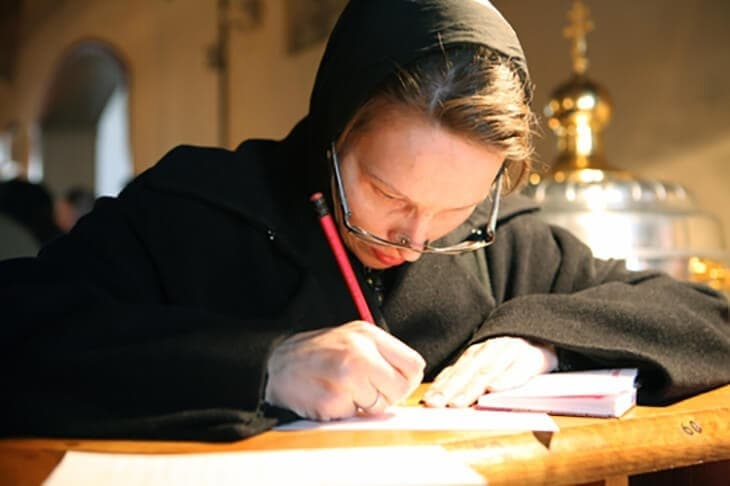 Женщина пишет записку в храме