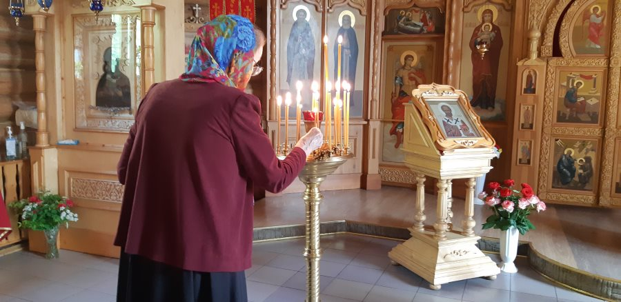 Служительница храма ставит свечи