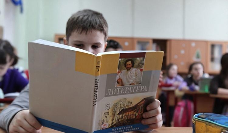 Мальчик держит учебник литературы в руках