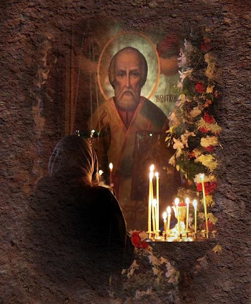 Женщина перед иконой святителя Николая в храме