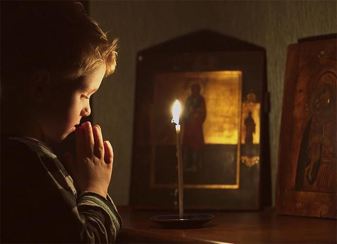 Мальчик молится дома
