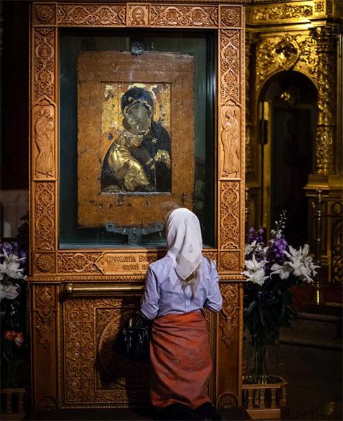 Женщина перед иконой Богородицы в храме