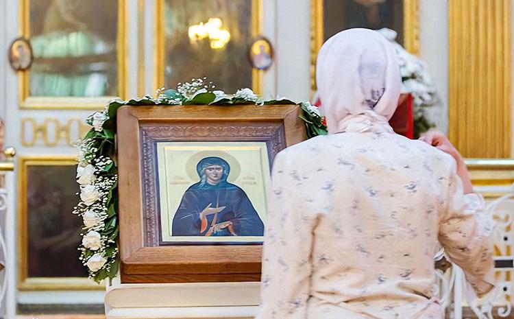 Женщина перед образом блаженной Ксении Петербургской