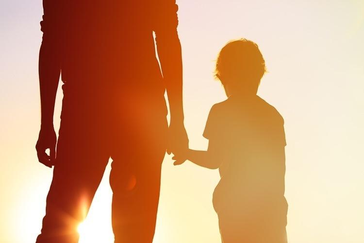 Держит ребенка за руку