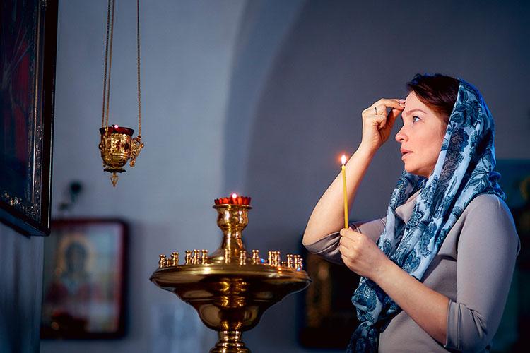 Молится у иконы в храме
