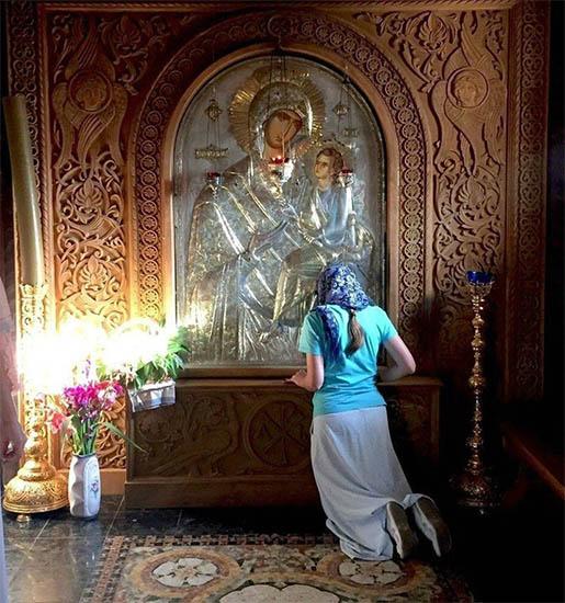 Женщина на коленях перед образом Богородицы