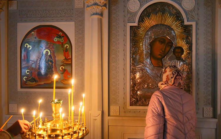 Женщина перед иконой Богородицы
