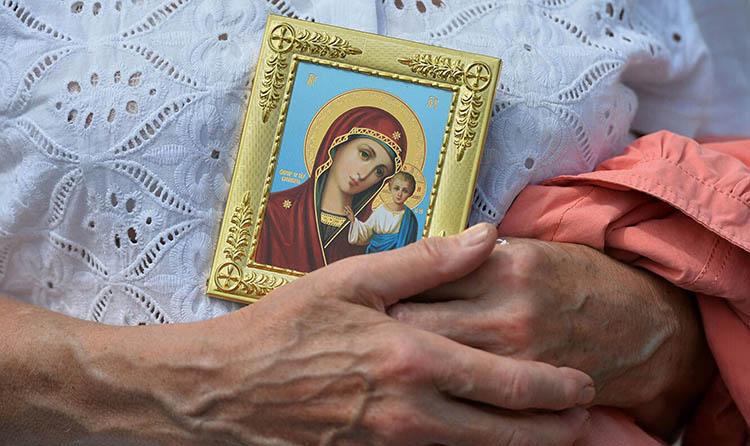 Женщина с иконой Богородицы в руках