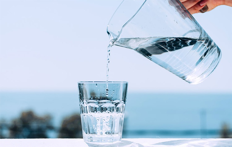 Наливает воду в стакан
