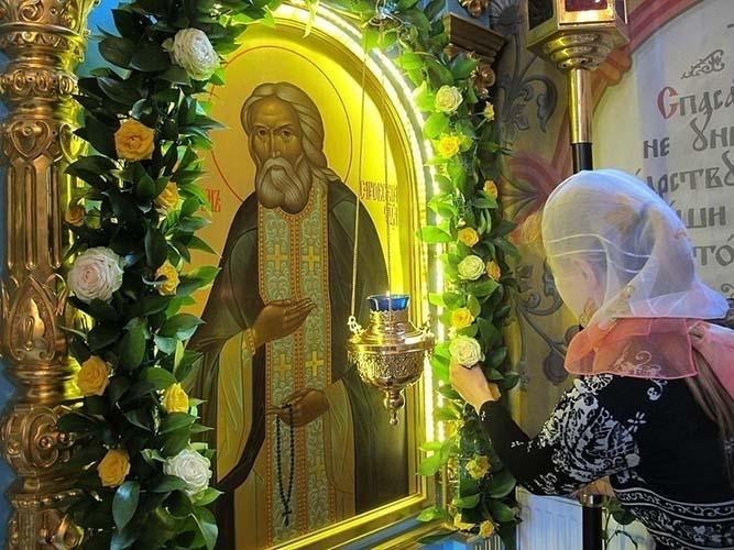Женщина перед образом преподобного Серафима Саровского
