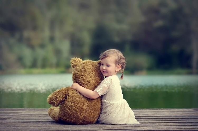 Девочка обнимает плюшевого медведя