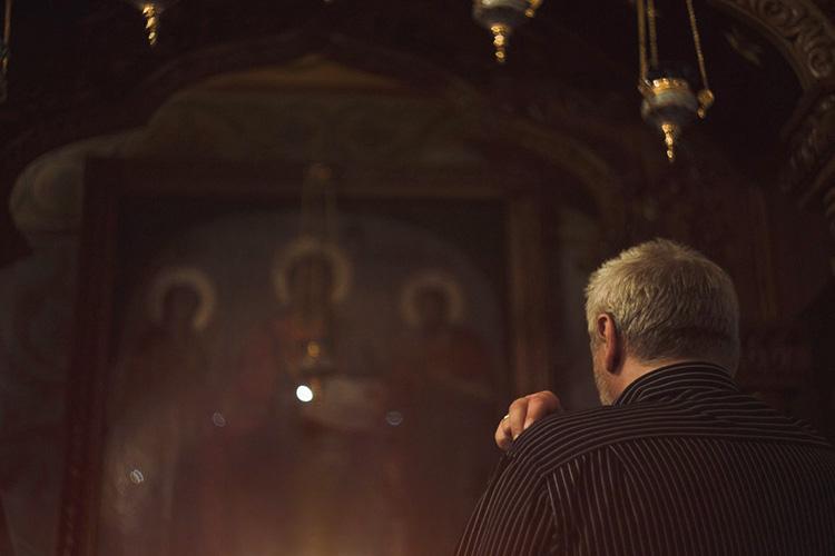 Мужчина молится в храме