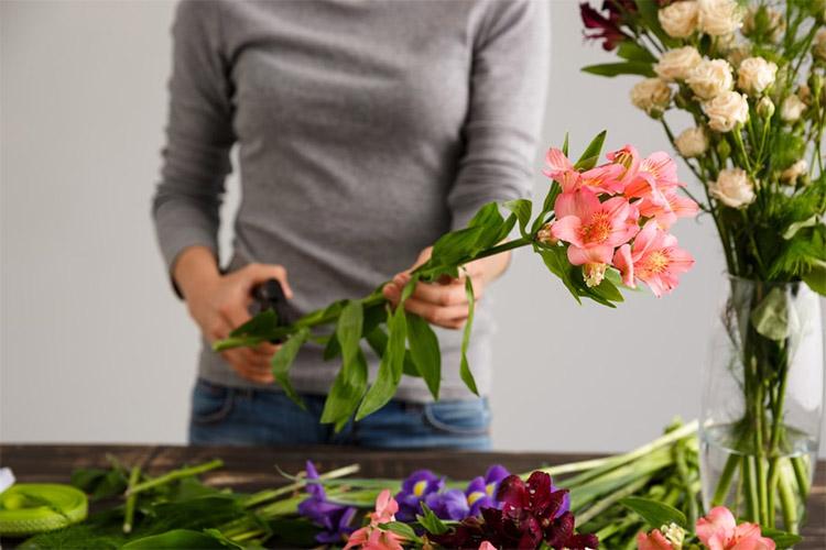 Женщина подрезает стебли цветов