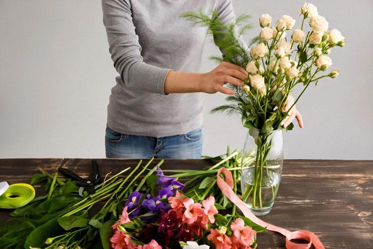 Женщина ставит цветы в воду